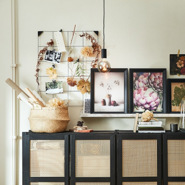 Dried flowers hanging from a SÖSDALA memo board and framed photos of flowers on a MOSSLANDA picture ledge above a sideboard.