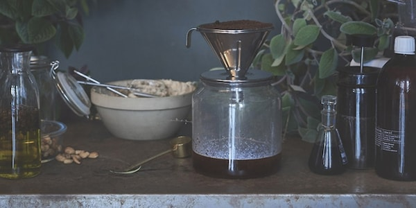 Drip coffee filtering into a glass jar on a table with other jars and ingredients.