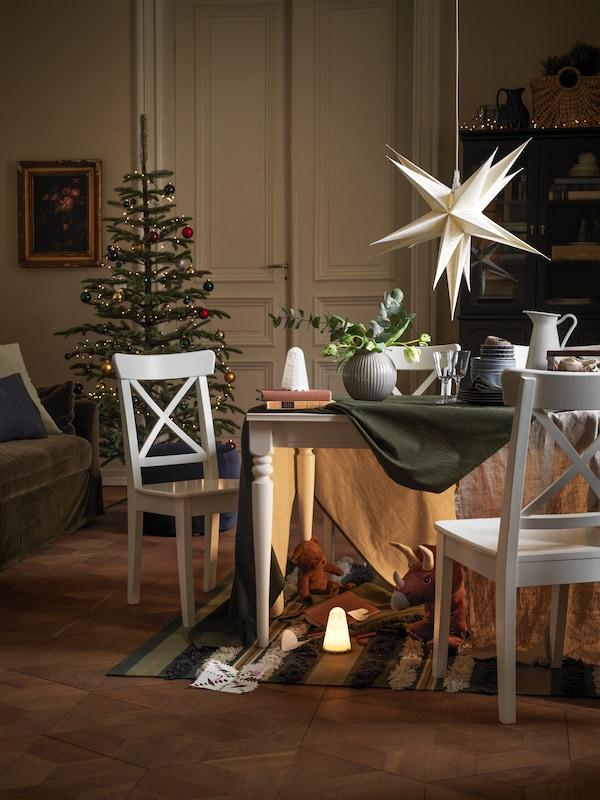Drzewko bożonarodzeniowe i stół jadalniany ustawione w udekorowanym na święta pokoju dziennym z urządzoną pod stołem sekretną jaskinią pełną zabawek.