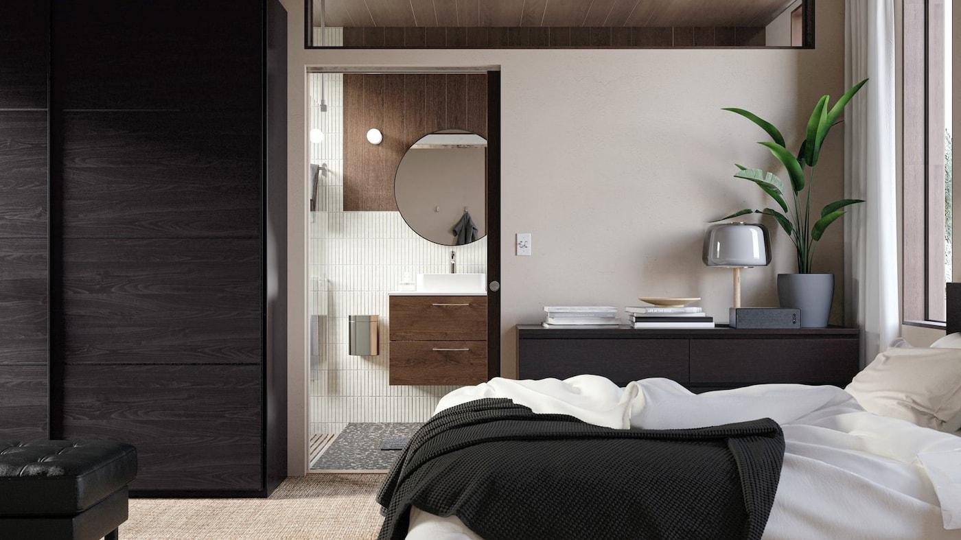 Drzwi prowadzące z sypialni do stylowo urządzonej łazienki z szafką pod umywalkę w kolorze drewna, okrągłym lustrem i beżowymi płytkami ceramicznymi.