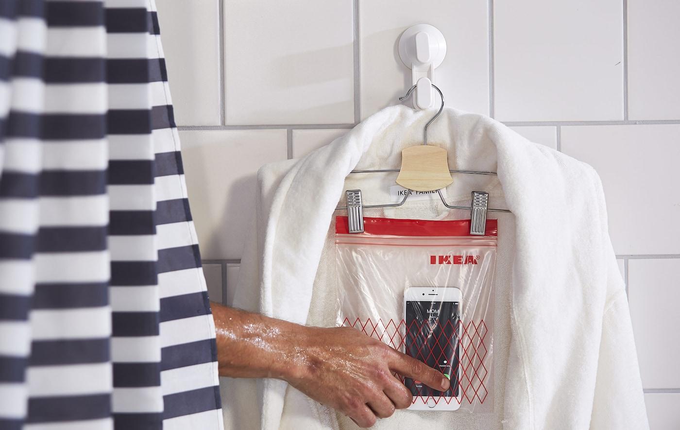 Du hättest gern im Bad einen Telefonhalter? Der lässt sich wunderbar mit IKEA Produkten wie BUMERANG Rock-/Hosenbügel basteln. Dafür packst du dein Telefon in einen Kunststoffbeutel, verschließt diesen und befestigst ihn am Bügel. Dein Telefon ist jetzt vor Wasserdampf geschützt.