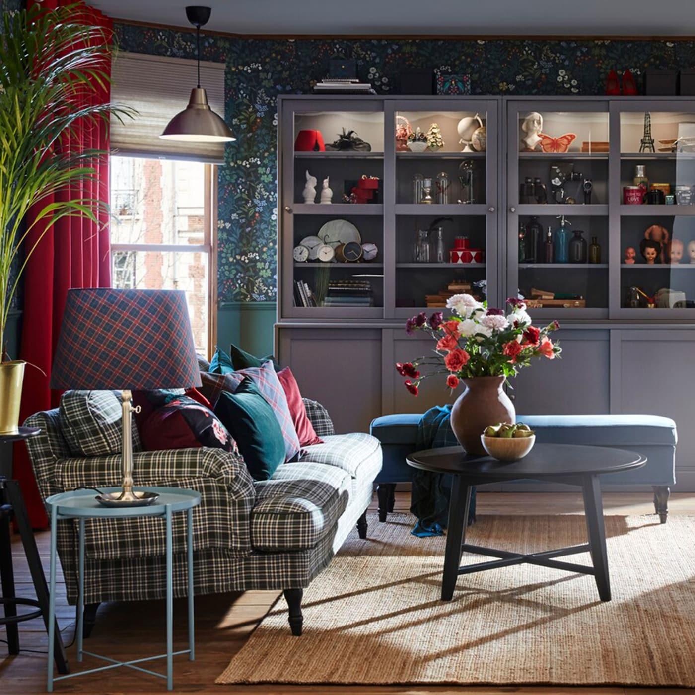 Du papier peint à motifs floraux aux plaids, ce couple ne craint pas d'exprimer son style dans le séjour. Le canapé IKEA STOCKSUND et le banc bleu vif en sont des exemples très parlants.