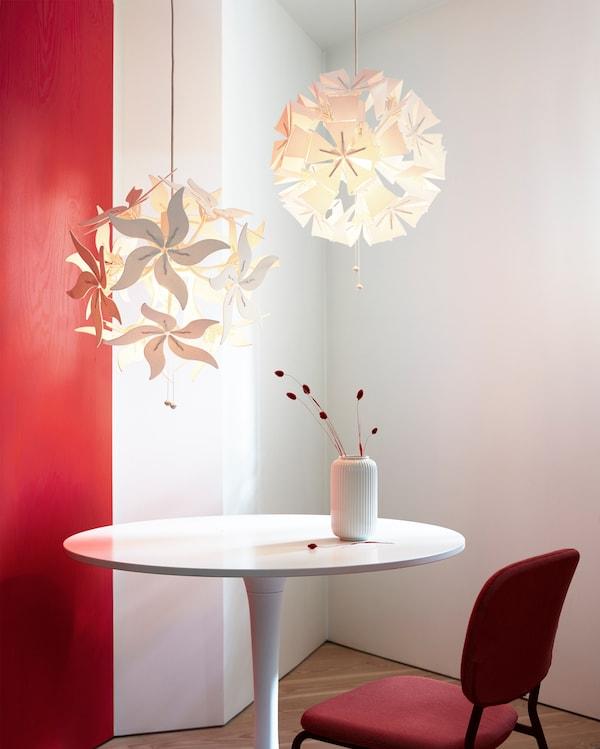 Dua lampu pendan RAMSELE yang menarik dalam bentuk bunga dan geometrik yang boleh dibuka apabila tali ditarik.