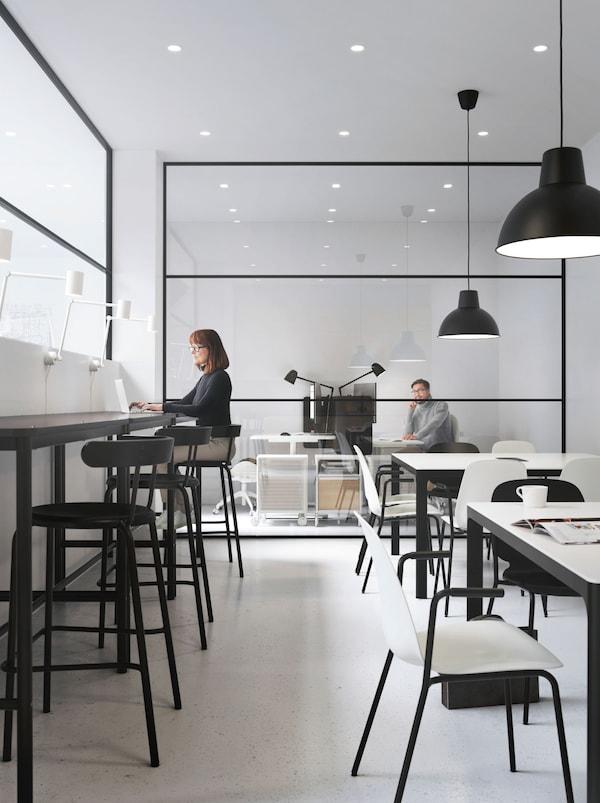 Duas áreas de trabalho – uma de estilo balcão com bancos altos, outra com mesas alinhadas. Ao fundo, um homem num gabinete envidraçado.