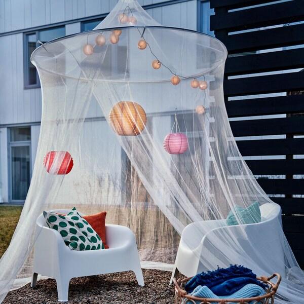 Duas cadeiras de exterior em branco, com almofadas coloridas, luzes em formato de globo e um dossel grande.