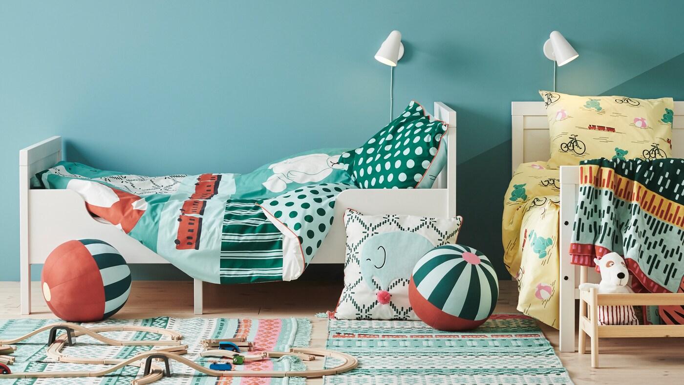 Dúas camas SUNDVIK con fundas de edredón e de almofada KÄPPHÄST nun dormitorio cun coxín e xoguetes polo chan.
