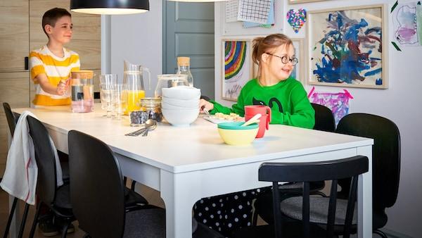 Duas crianças, um menino e uma menina, sentados numa mesa de refeição extensível EKEDALEN branca.