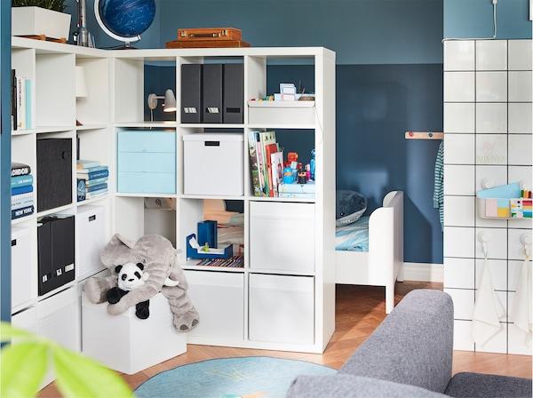 Duas estantes servem de divisória ao mesmo tempo que oferecem imenso espaço de arrumação. Ao fundo, uma cama de criança.