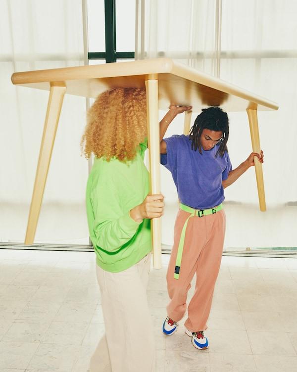 Dúas persoas novas transportan a mesa MARKERAD sobre as súas cabezas.