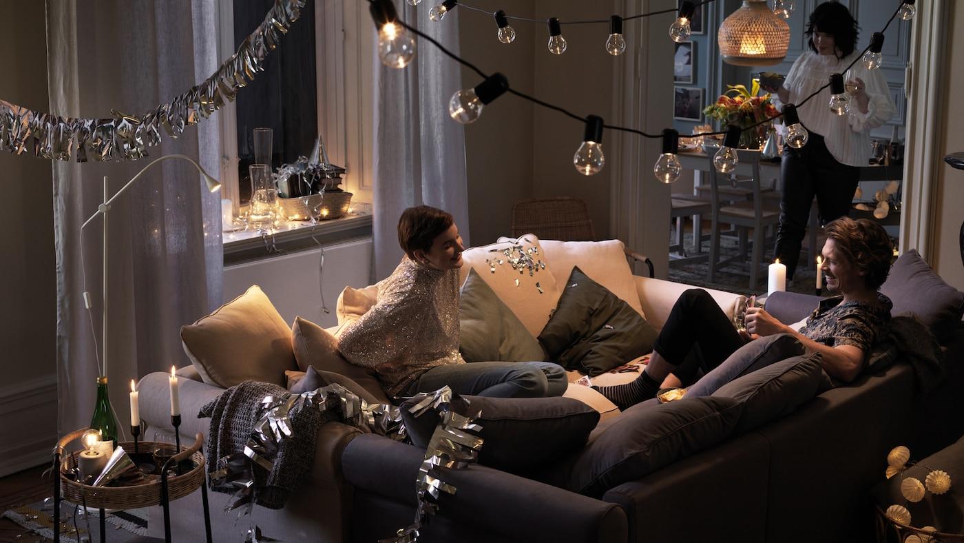 Dúas persoas sentadas xuntas en dous sofás pegados no medio dun cuarto, falando e rindo.