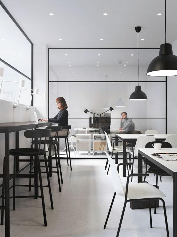 Due aree di lavoro, una con tavoli e sgabelli alti, che ricordano il bancone di un bar, l'altra con tavoli e sedie di altezza normale. L'ufficio in fondo ha una parete a vetri – IKEA