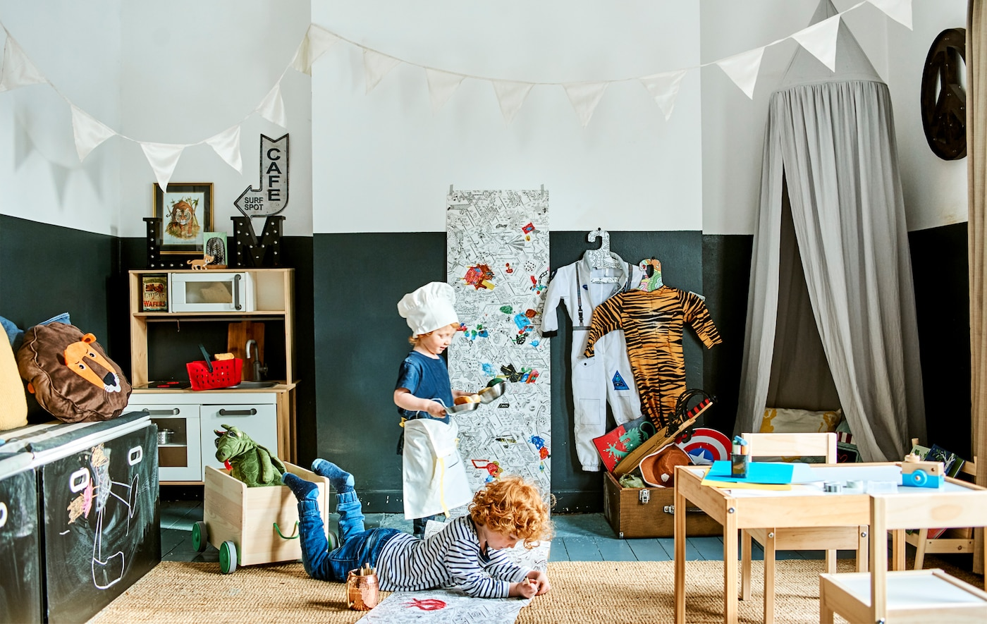 Due bambini giocano in una stanza con un tavolo e sedie per bambini, una lavagna, una cucina gioco e bandierine decorative - IKEA