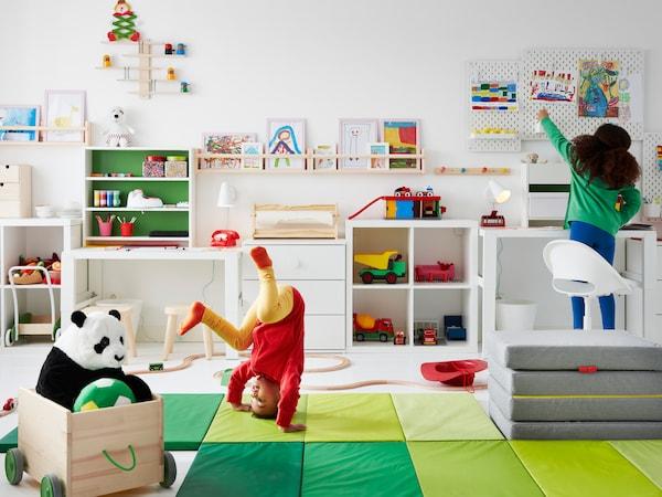 Due bambini, uno dei quali fa una capriola su un tappetino da ginnastica PLUFSIG, in una stanza piena di giochi, con mobili bianchi e disegni sulle pareti.