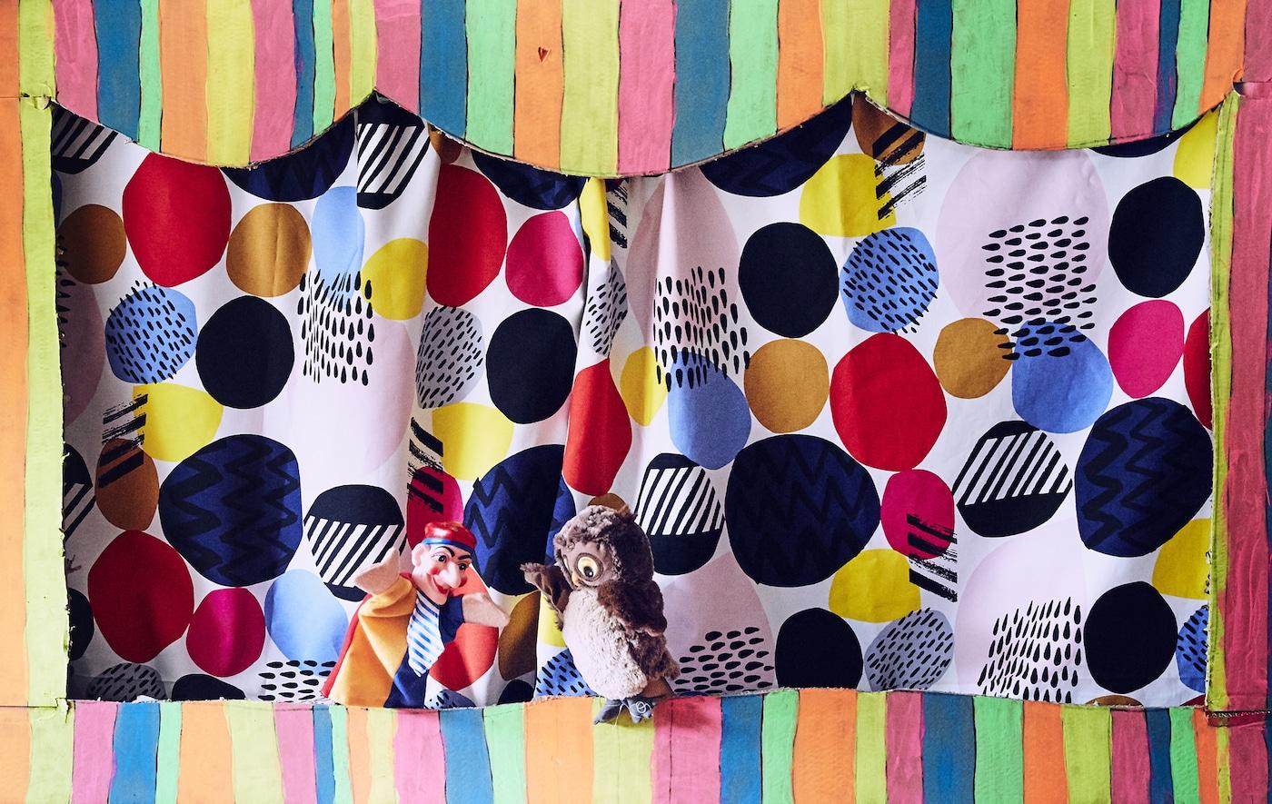 Due burattini su uno sfondo colorato all'interno di una vivace cornice di cartone a righe - IKEA