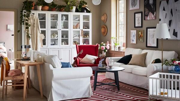 Due divani EKTORP posizionati l'uno di fronte all'altro, in un soggiorno moderno e al tempo stesso tradizionale dove dominano il bianco e il rosso.