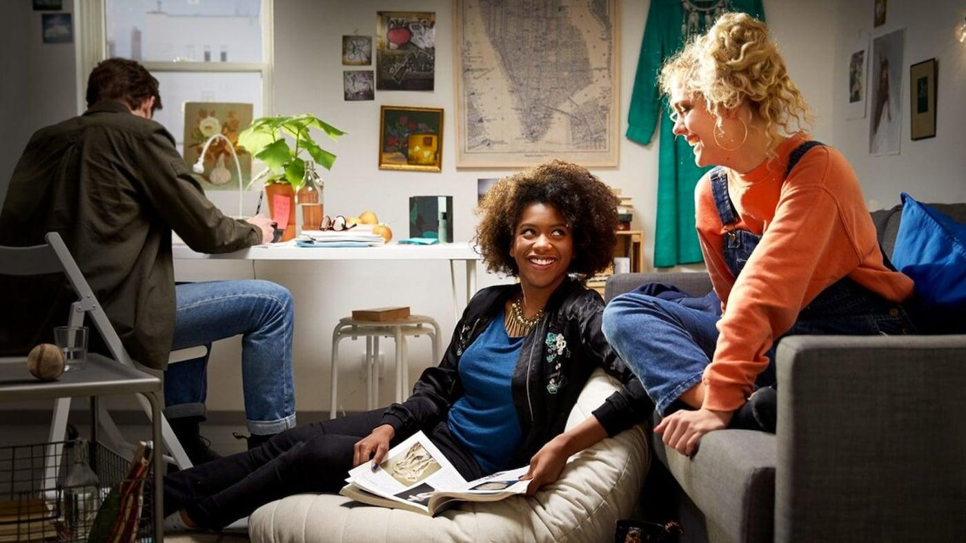 Due donne stanno uscendo insieme. Uno è seduto su un divano e l'altro su un cuscino del pavimento.