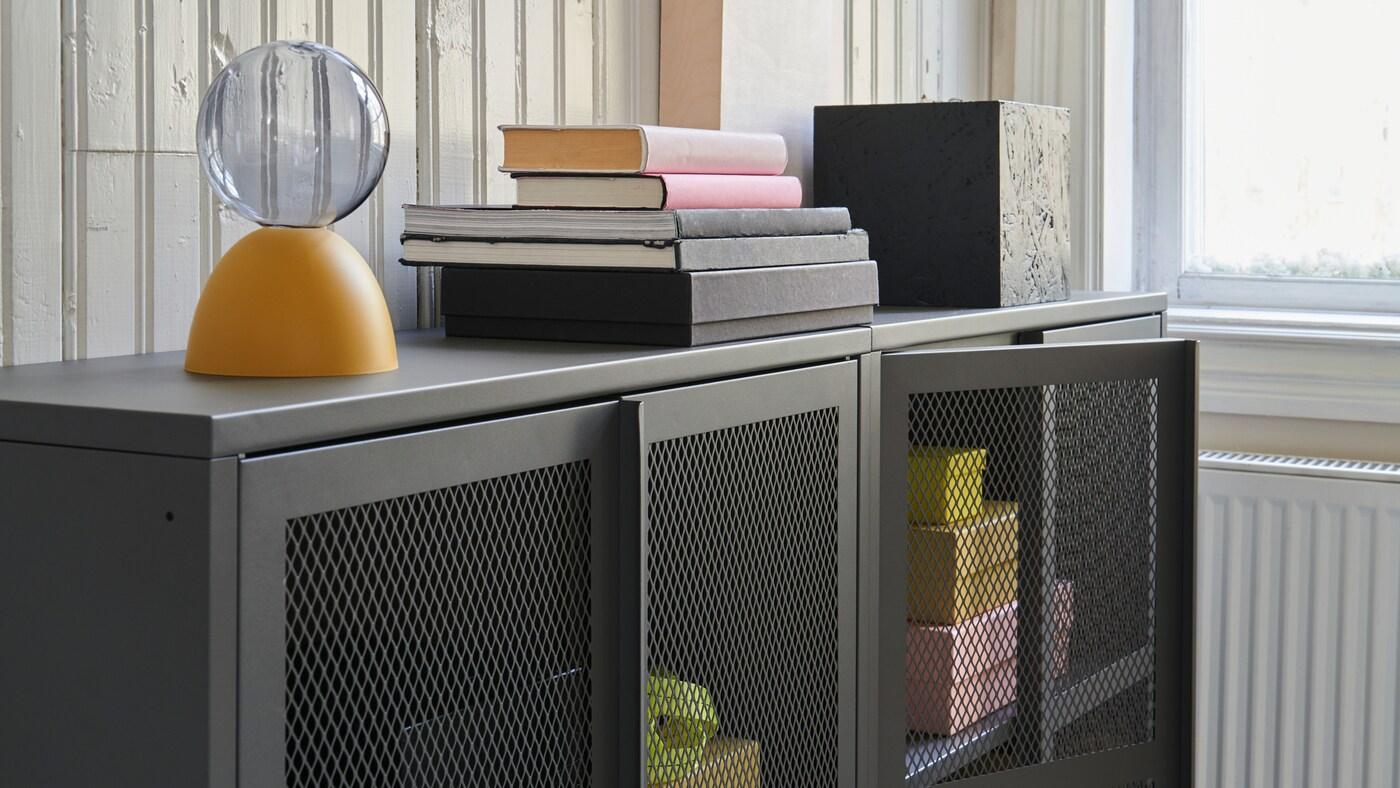 Due mobili IVAR in grigio con ante dotate di rete metallica da cui si intravedono oggetti gialli e rosa.
