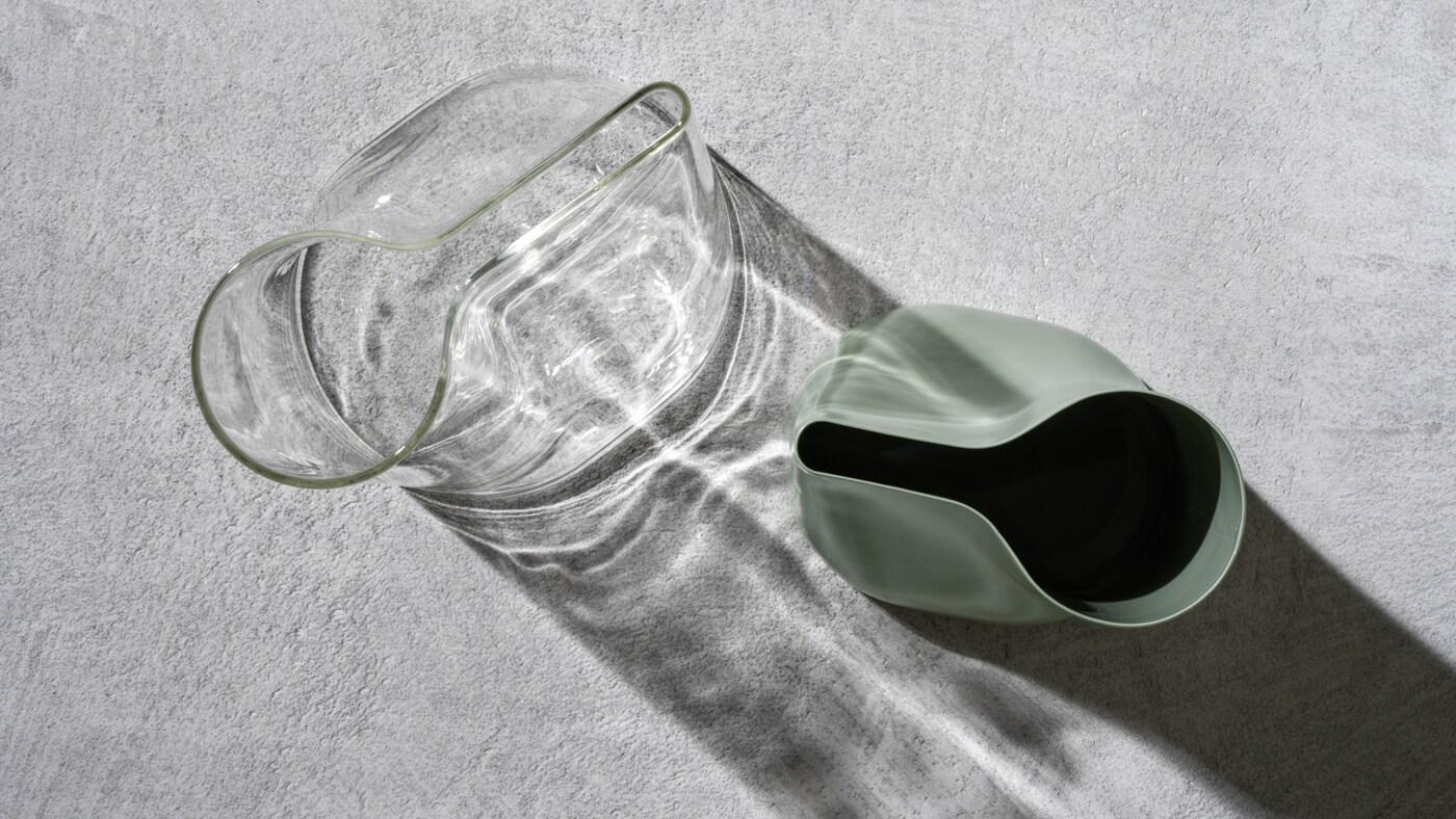 Due vasi/annaffiatoi CHILIFRUKT in vetro trasparente e verde acciaio su una superficie in cemento grigio.