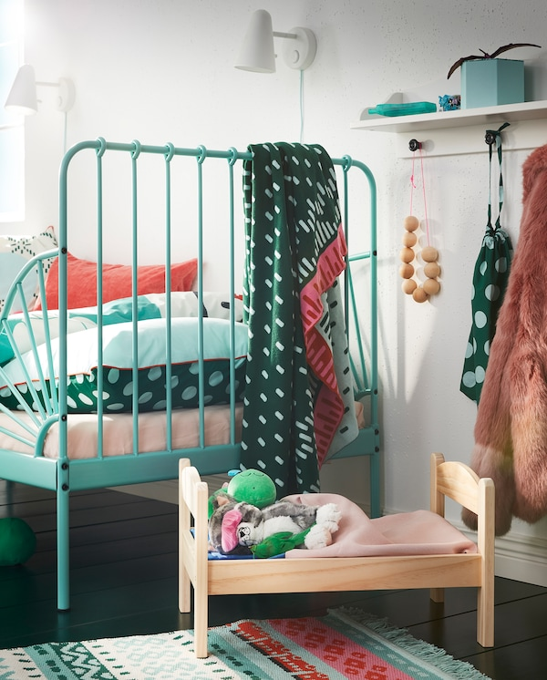 DUKTIG krevet za lutke od pune borovine, s posteljinom i plišanim igračkama pored tirkiznog dečjeg kreveta.