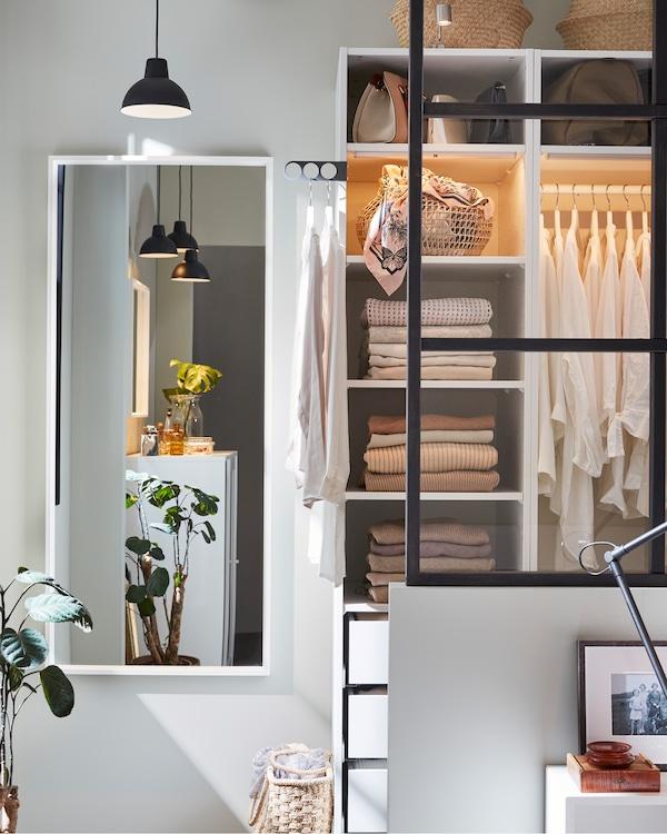 Dulap alb, o lampă suspendată neagră, o oglindă albă și o plantă verde.
