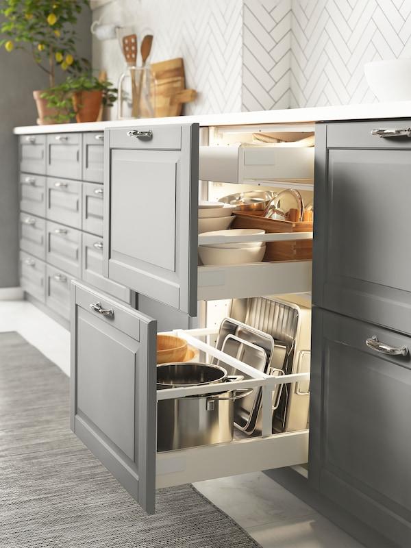Dulapuri de bază într-un cadru de bucătărie cu fronturi de sertar gri, două sertare sunt deschise și au în interior veselă și tacâmuri.