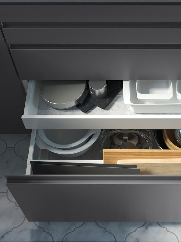 Dulapuri de bucătărie cu fronturi de sertare gri închis. Un sertar este deschis și se vede un alt sertar în interior, în ambele se află ustensile de gătit.