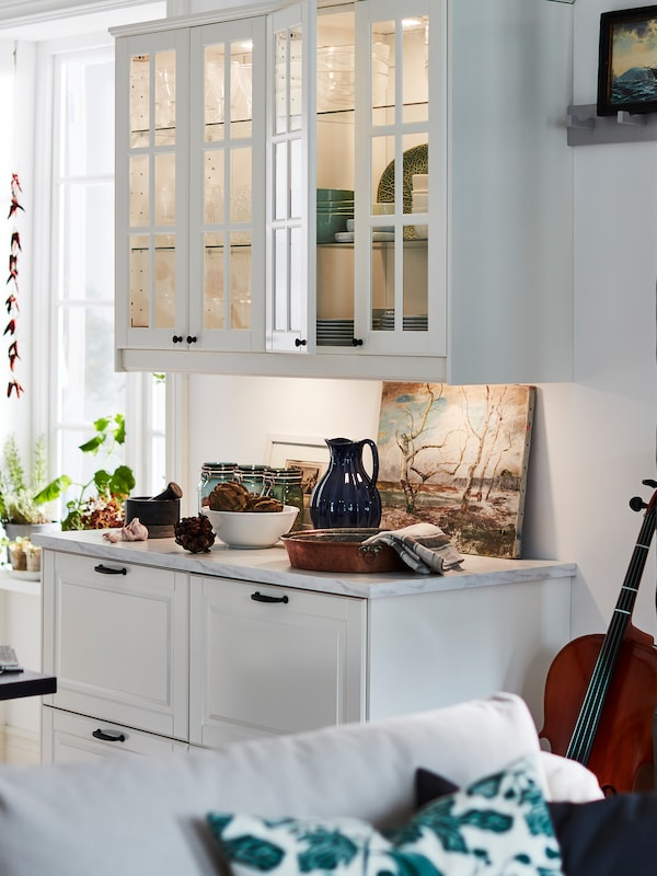 Dulapuri de bucătărie cu uși în nuanțe de alb, un blat alb cu efect de marmură/cuarț și sertare mari în nuanțe de alb.