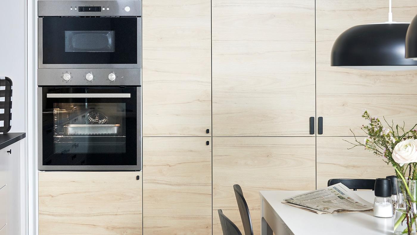 Dulapurile de bucătărie IKEA METOD montate pe perete cu uși ASKERSUND cu efect de frasin deschise la culoare și un cuptor și cuptor cu microunde încorporate.