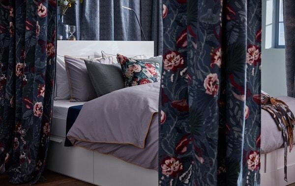 Dunkelblaue Vorhänge aus FILODENDRON Stoff mit Blumenmuster von IKEA umrahmen ein Bett.