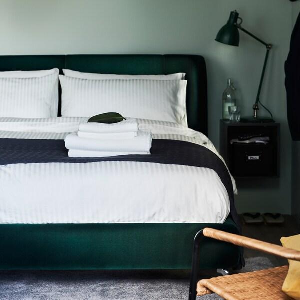 Dunkelgrünes Polsterbett mit weißer Bettwäsche