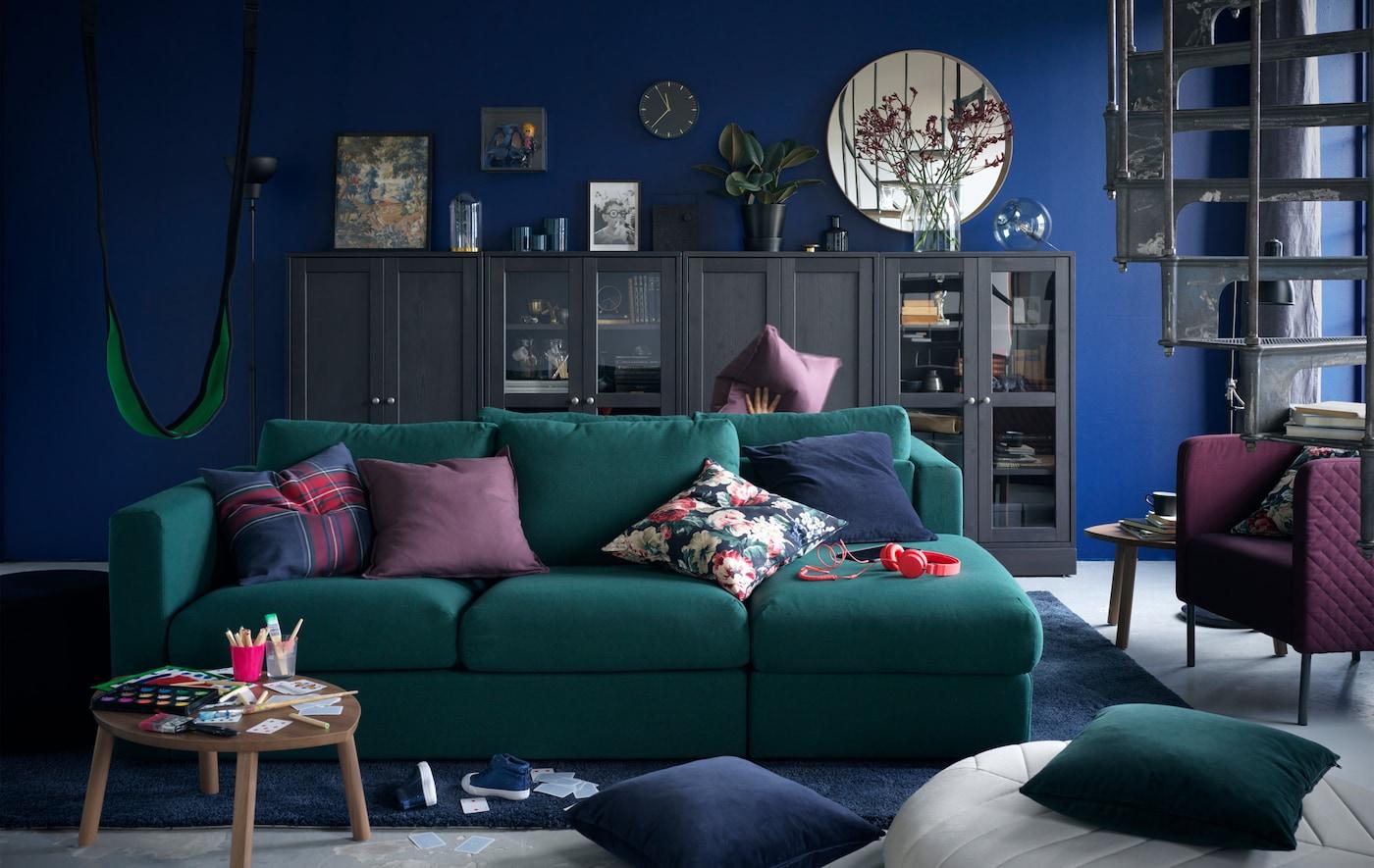 Dunkelgrünes VIMLE Sofa in einem Wohnzimmer mit grauer Vitrinen-Kommode vor einer dunkelblauen Wand
