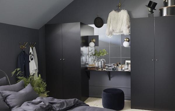 Durch dunkle Möbel wirkt das Schlafzimmer größer. Hier haben wir einen Schminktisch zwischen zwei PAX Kleiderschränken in Schwarzbraun gestaltet. Die Wand über dem Tisch ist mit vielen Spiegeln versehen. Die PAX Kleiderschränke haben schwarze Fronten und viel Platz im Inneren.