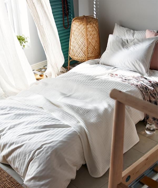 Dušek napravljen za spavanje na podu pored otvorenih prozora, ugao praznog okvira kreveta koji nagoveštava privremeno rešenje za spavanje.