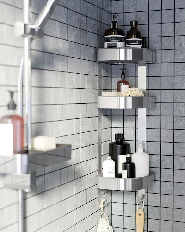 Душ із сірою плиткою та кутова навісна полиця з нержавіючої сталі, де зберігаються гелі для душу, шампуні та інші речі.
