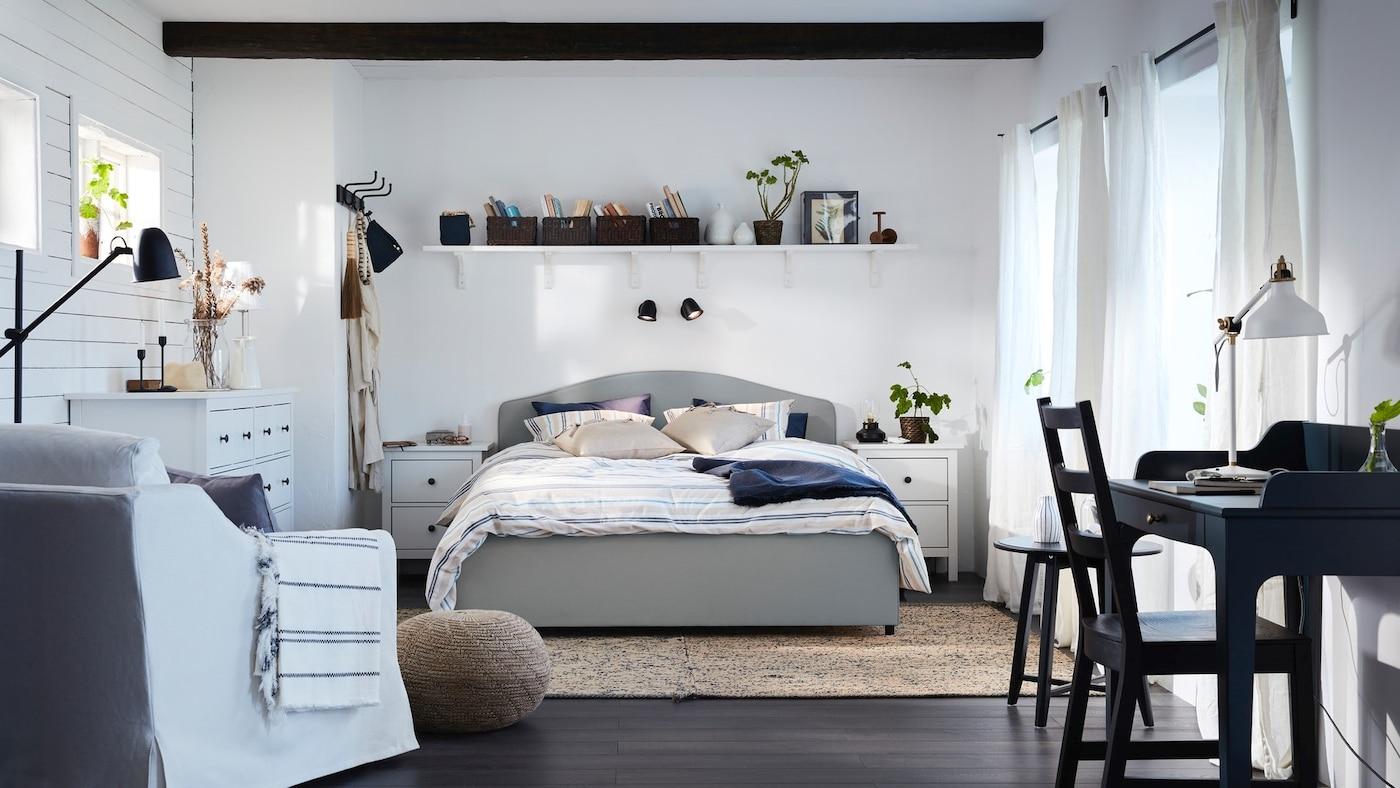Duża, biała sypialnia z tapicerowanym łózkeim Hauga i białym fotelem.