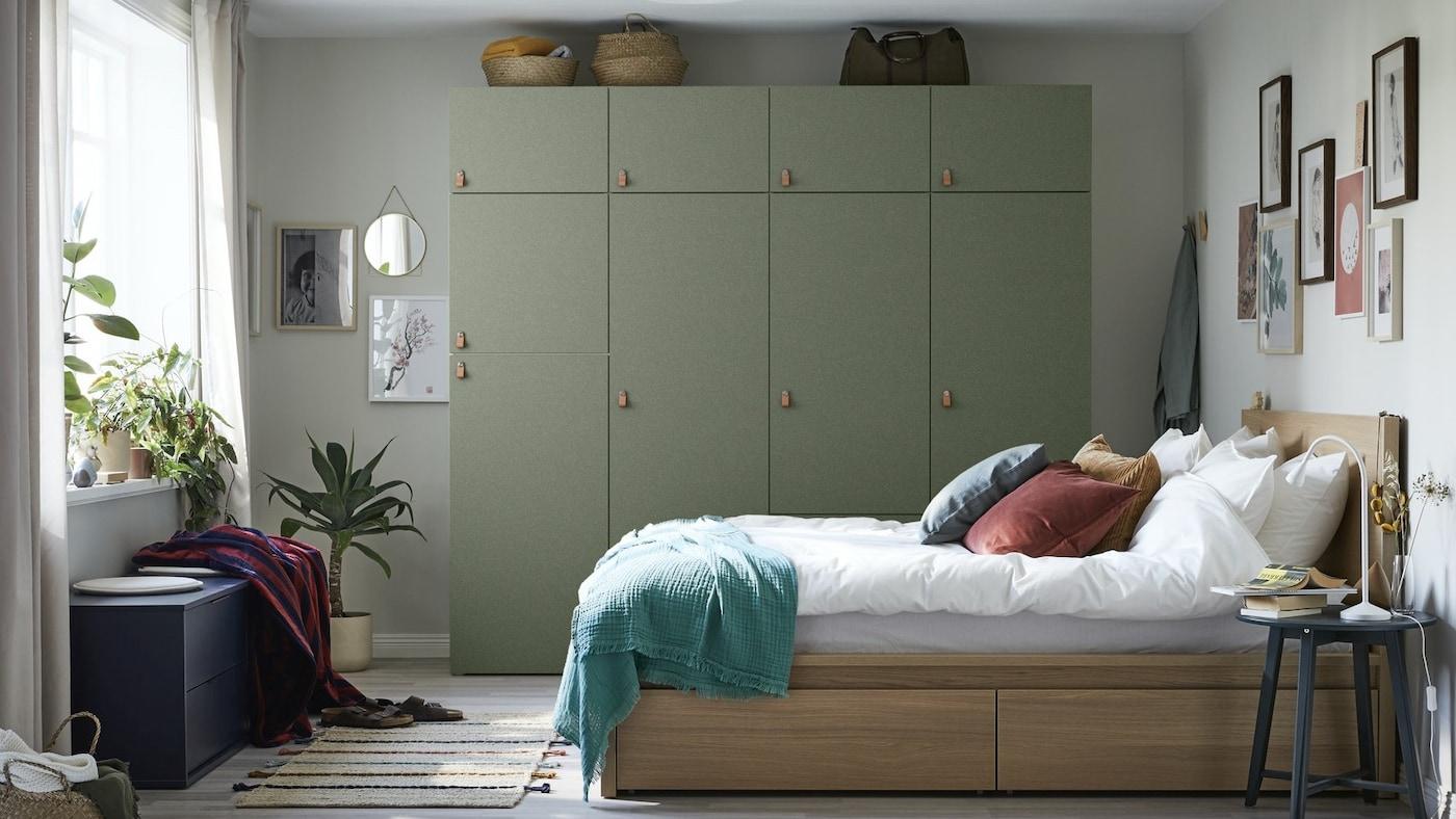 Duża zielona szafa ustawiona pod szarą ścianą. Łóżko w kolorze drewna z białą pościelą oraz czerwonymi, niebieskimi i brązowymi poduszkami.