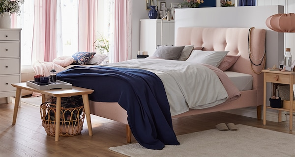 Duże, szare łóżko tapicerowane z wyściełanym zagłówkiem ustawione pod przepierzeniem wydzielającym garderobę typu walk-in.
