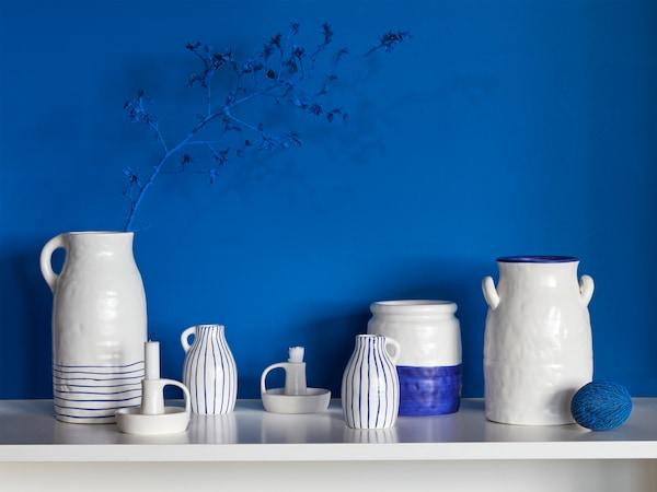 Dużo wazonów GODTAGBAR wykonanych z kamionki i ręcznie malowanych na biało-niebiesko, a także świecznik z tej samej serii.