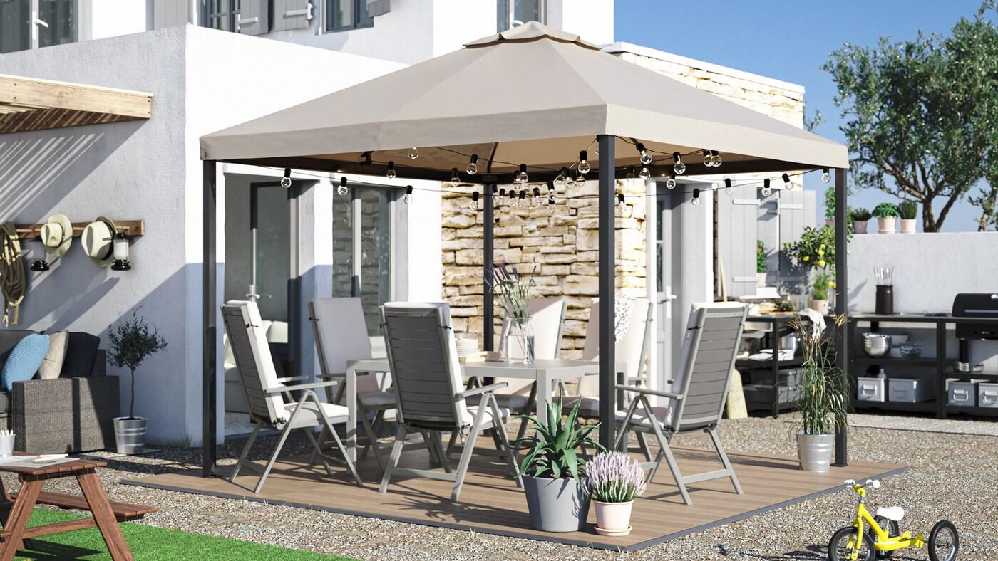 Duży ogródek ze stołem jadalnym, krzesłami ogrodowymi z poduszkami, altaną, drewnopodobną płytą podłogową i zewnętrzną kuchnią.