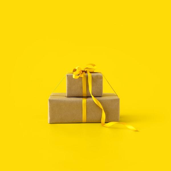 Dva dárky se stuhou na žlutém pozadí.