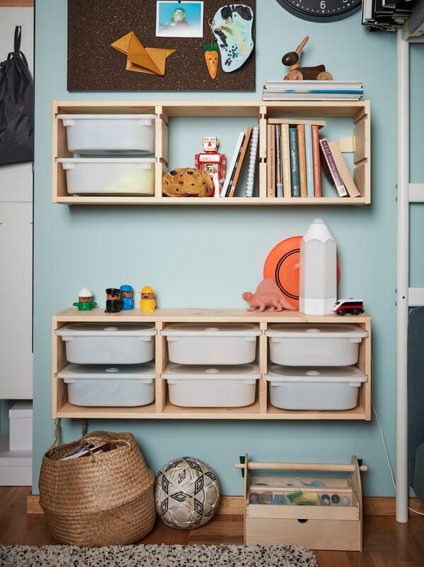 Dva elementa za zidno odlaganje iz dečje serije TROFAST, koja sadrži drvene okvire i bele plastične kutije.