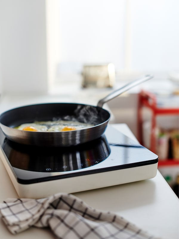 Dva jajeta se prže na TILLREDA prenosivoj indukcijskoj ploči na radnoj ploči, a kuhinjska krpa je pored.