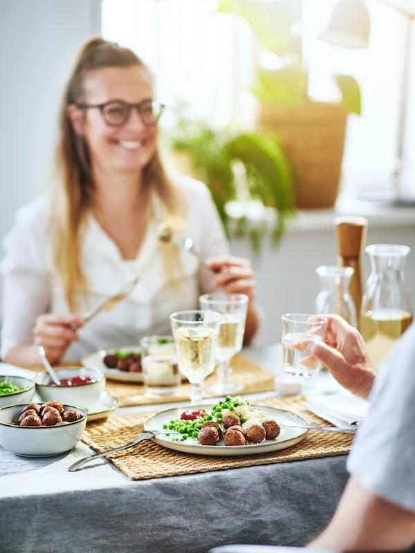 Dva lidé u stolu jedí kuličky IKEA.