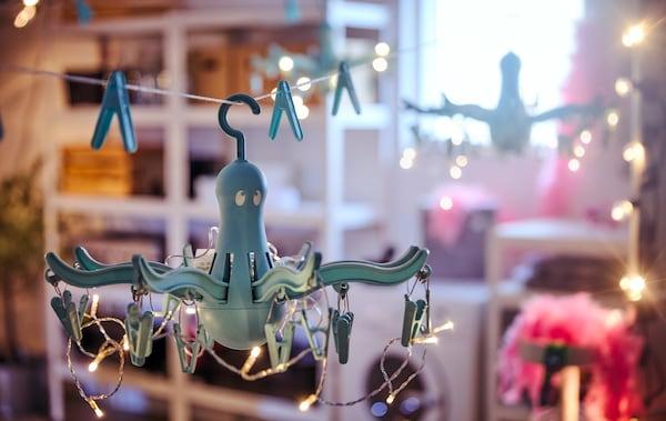 Dva lustre vyrobené zo sušiakov a svetelných reťazí zavesených v garáži s práčkou a rôznymi úložnými priestormi.