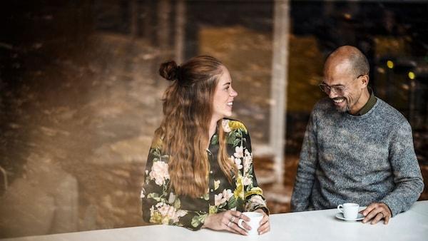 Dva mladí lidé si spolu povídají nad šálkem kývy.