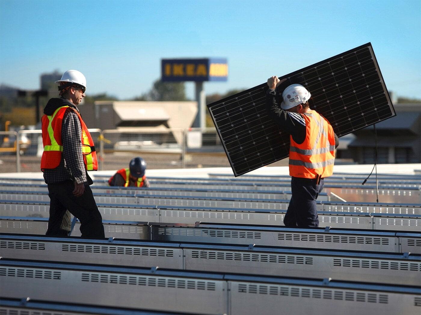 Dva muži pokládající solární panely na pole.