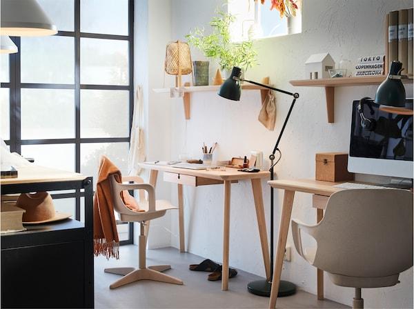 Два письмові столи, виготовлені з ясеневого шпону з білим та бежевим обертовими стільцями, між ними розміщено чорний торшер та дві навісні полиці, виготовлені з ясеневого шпону.