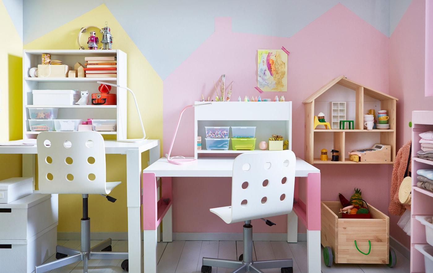 Два регулируемых письменных стола и стула стоят рядом в общей детской