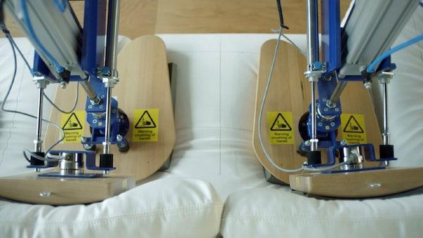 Dva roboti na laboratorní zkoušce IKEA napodobující dvě sedící osoby a testující trvanlivost pohovky.