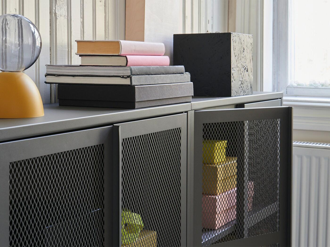 Два серых шкафа ИВАР с полупрозрачными сетчатыми металлическими дверцами с несколькими желтыми и розовыми предметами.